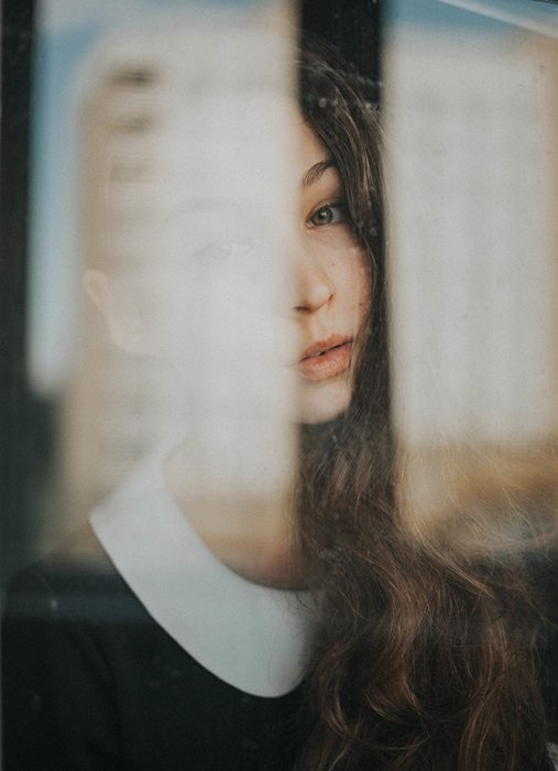 Portrait photo of a woman shot through a window
