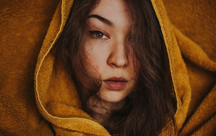 Portrait photo of a woman covered in a blanket