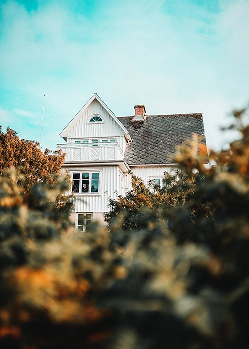 Photo of a house with bushes in the foreground