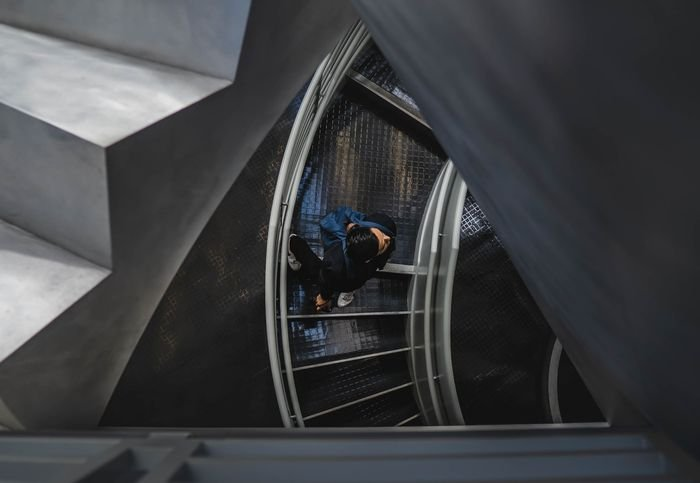 Photo of a guy walking up on a spiral stairway