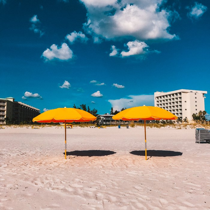 A photo of a beach composition with two orange umbrellas in the middle