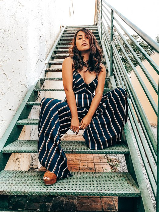Full body-length photo of a girl sitting on a stairs with leading lines