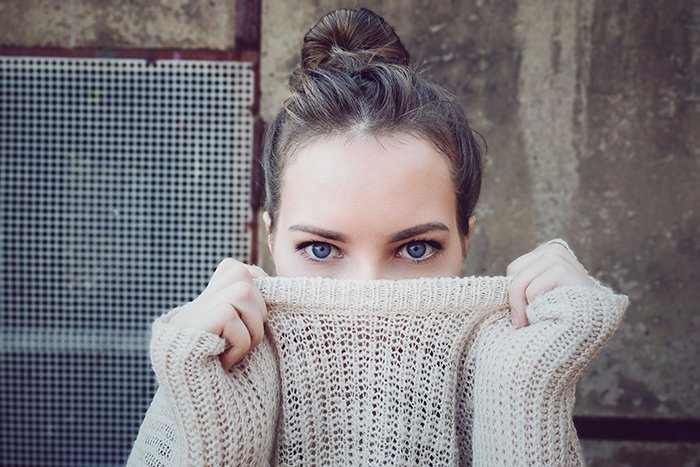 Portrait photo of a woman with blue eyes pulling her sweater in front of her mouth