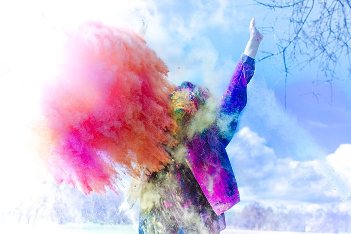 Photo of a man in coloured jacket with a cloud of orange powder in front of him