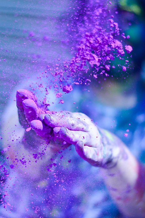 Close-up photo of a pair of hands throwing purple colour powder