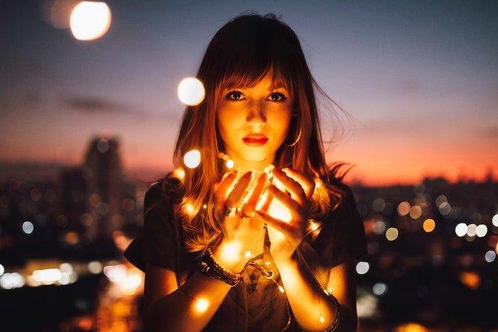 Girl holding fairy lights to illuminate her face