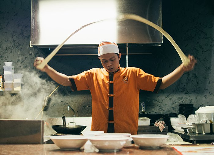 Motion blur photo of an Asian cook