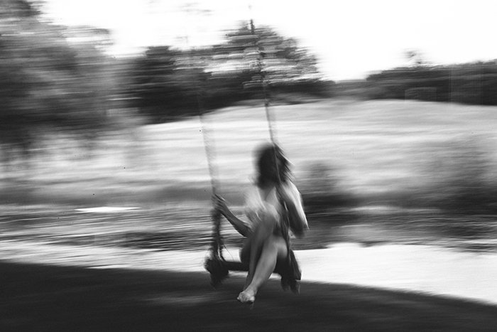 Motion blur photo of a woman on a swing