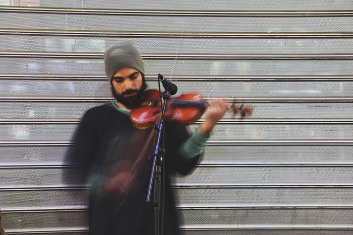 Motion blur photo of a man playing the violin