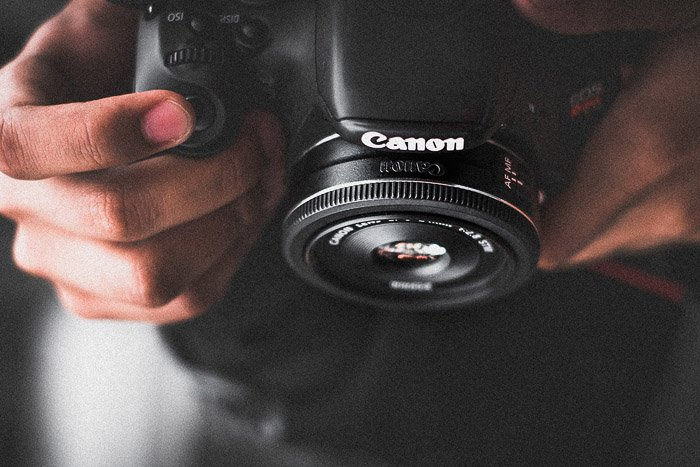 A close up of a photographer holding a Canon DSLR with Pancake lens