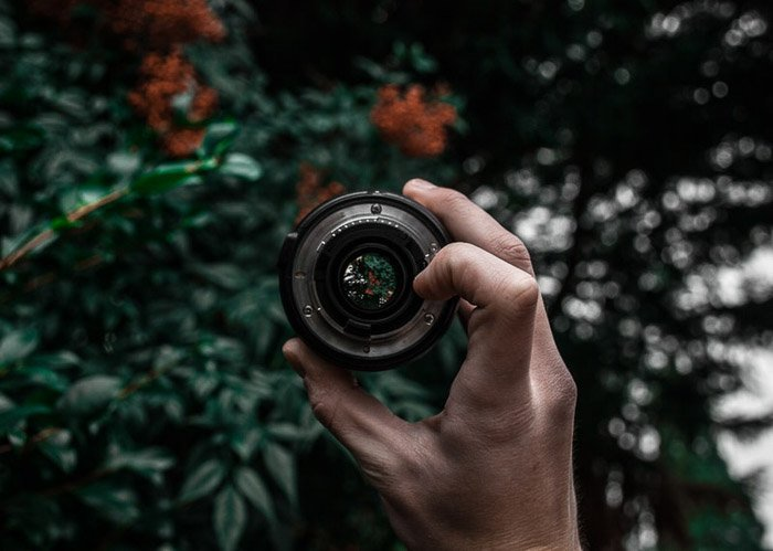 a person holding a pancake lens outdoors