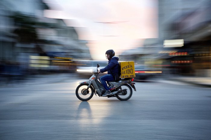 Photo of a man riding a motorcycle with panning photography effects