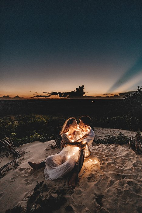 atmospherically lit outdoor portrait of a couple posed on a beach with fairy lights