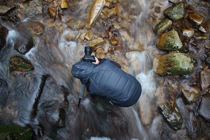 a high angle photo of a photographer setting up gear for taking waterfall photography