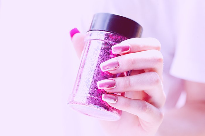 cool nail photography of a female model with painted nails holding a tub of glitter