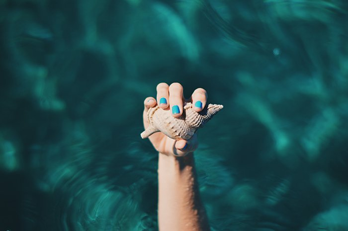 cool nail photography of a female model with painted nails holding a seashell