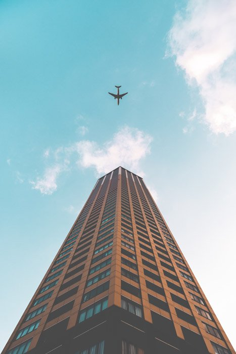 Photo of an airplane and a tall building from an upward-facing perspective