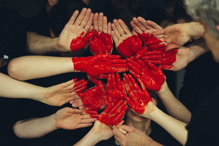 Photo of many pairs of hands painted red forming the shape of a heart