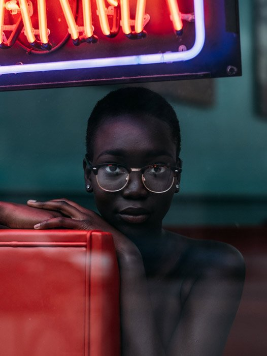 Portrait photo of a woman with glasses sitting on a red sofa behind a restaurant window