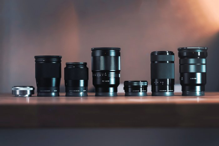 a range of Sony lenses on a shelf, highlighting the different Sony lens abbreviations