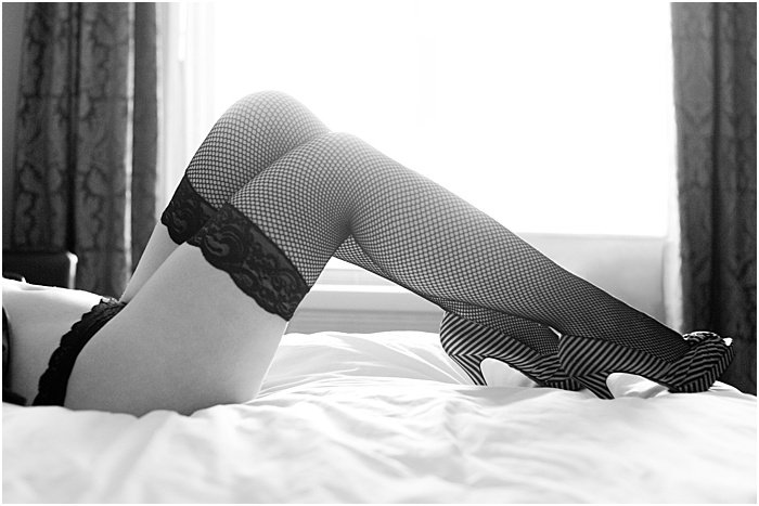 Boudoir photo of the legs of a woman in fishnet stockings