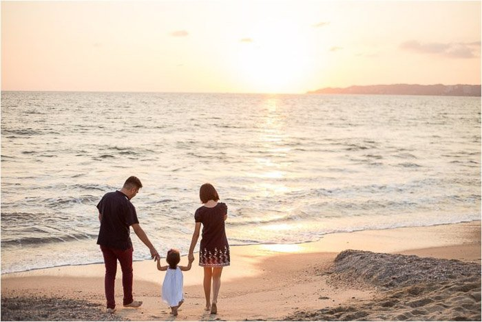 sweet family portrait of parents holding a little girls hand outdoors on the beach
