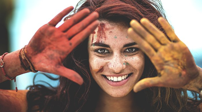 Young woman holding paint covered hands up to frame her face.