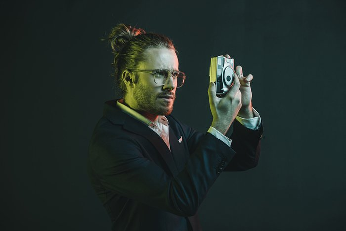 A man holding a camera and looking through the lens in front of a dark background