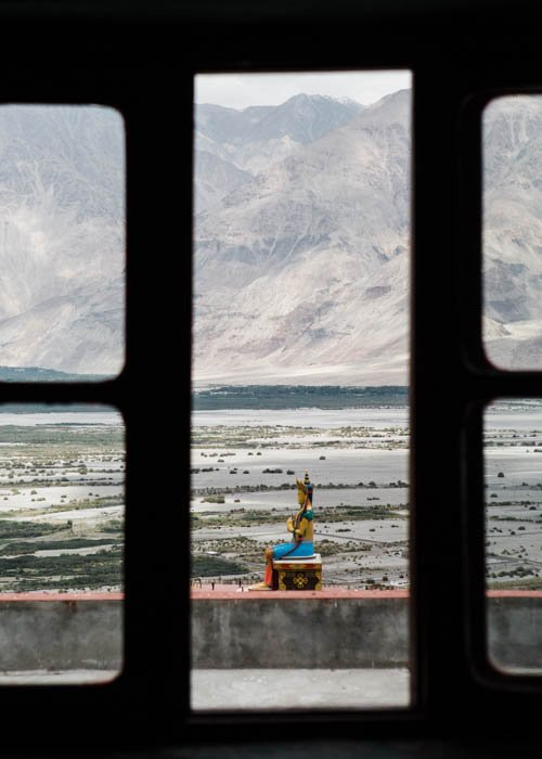 Photo of a buddhist statue shot from a window with mountains in the background