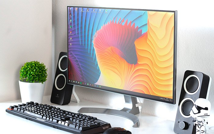 A colourful photo editing monitor on a desk- best monitors for photo editing