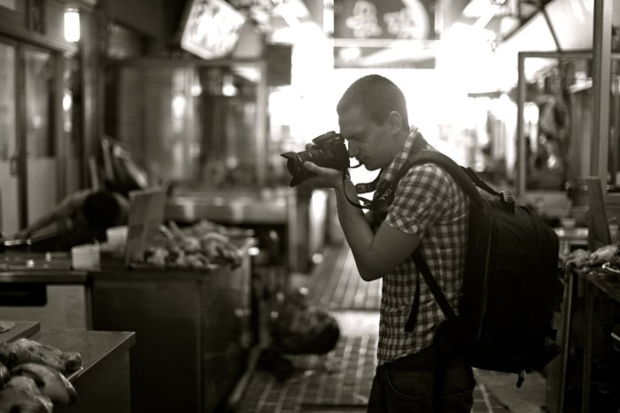 A photographer with a camera and backpack