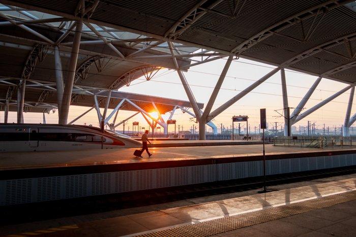 A man walking along a platform at a train station