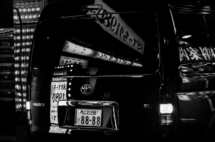 Black and white image of the back of a black van with reflections from the buildings around