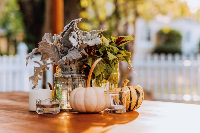 Still life image with candles and pumpkins around decorative foliage in vases