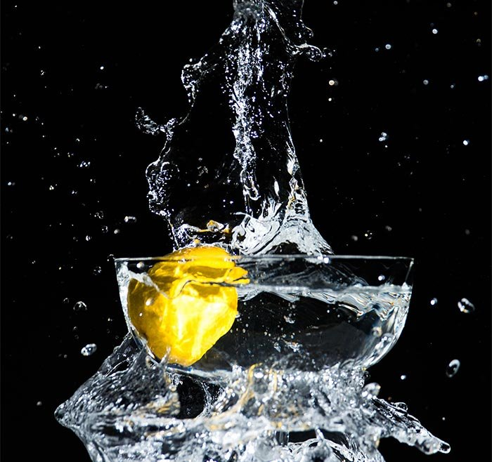 A photo of a lemon dropped into a bowl of water, causing a splash
