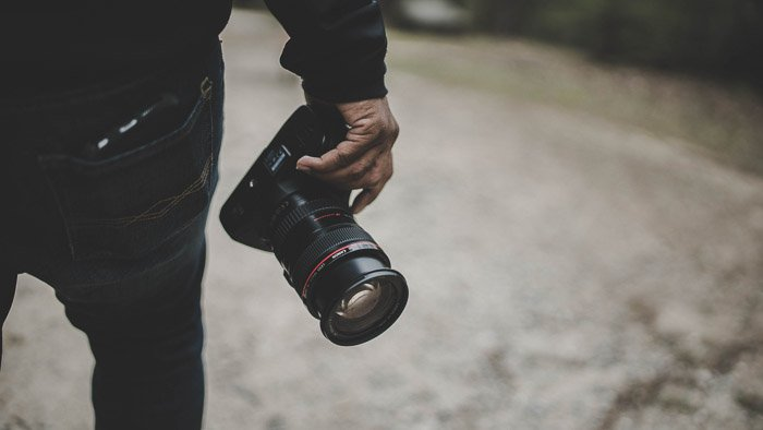 photographer holding the cheapest full frame dslr by his side