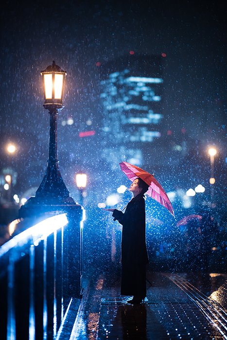 Photo of a woman standing under an umbrella in the snow with blue lights in the background