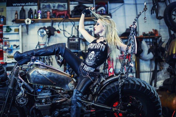 a girl in biker gear posing on a motorbike