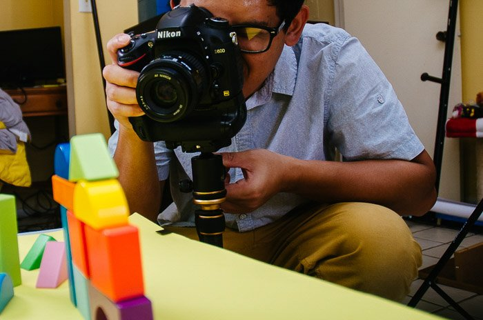 a man photographing toy building blocks with a Nikon DSLR