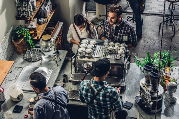 an overhead shop of baristas working in a busy coffee shop