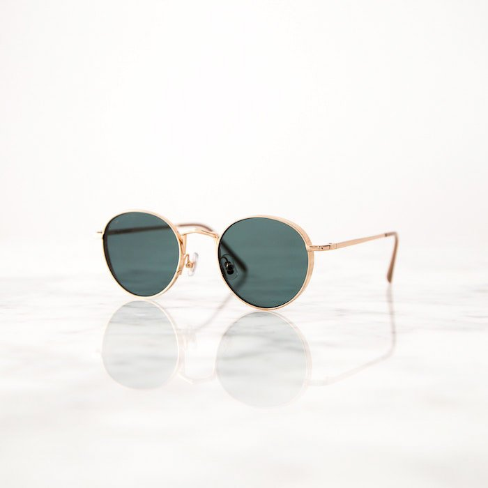 a pair of gold rimmed sunglasses on a reflective white surface