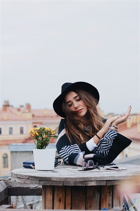 a stylish young woman sitting at a wooden table outdoors