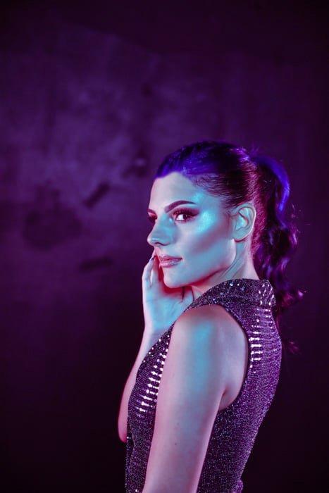 atmospheric portrait of a woman indoor under purple light