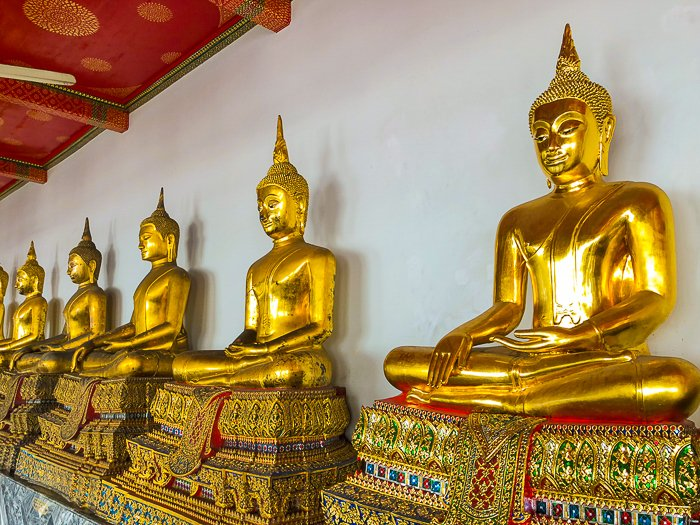a row of ornate golden buddhas