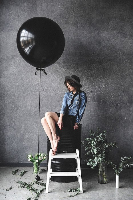 portrait of a stylish female model sitting by a black balloon