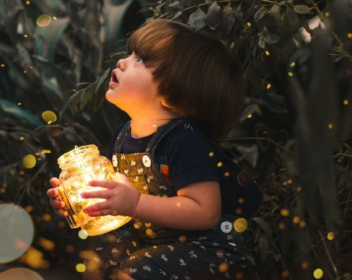 Child holding jar with fairy lights captured with bokeh photography effect