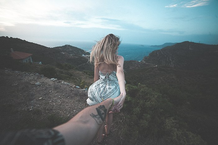 A woman walking through a luscious landscape holding her partners hand