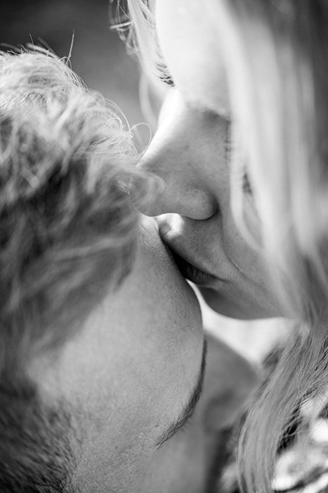 A black and white shot of a couple kissing