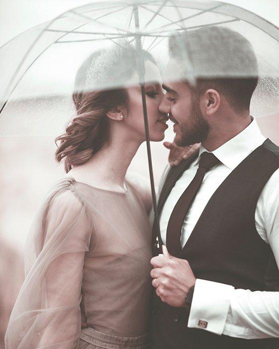 Romantic shot of a young couple posing under an umbrella