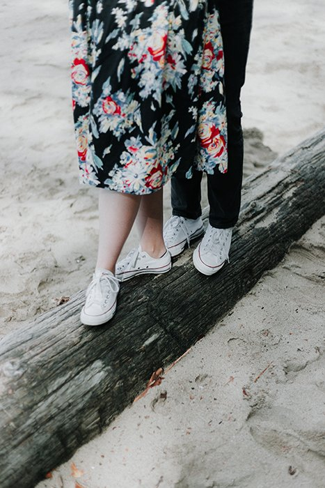 a close up of a couples legs balancing on a wooden beam
